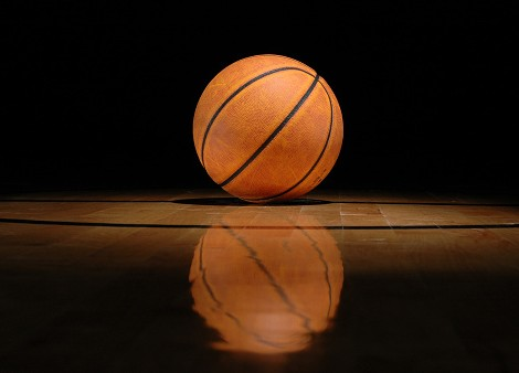 Basketball lying on shiny court against black background